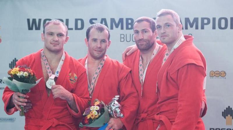Viktors Reško (pa labi) uz pasaules čempionāta goda pjedestāla. Foto: sambo-fias.org