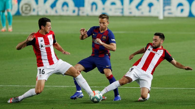 Arturs laužas starp diviem pretinieku futbolistiem. Foto: Reuters/Scanpix